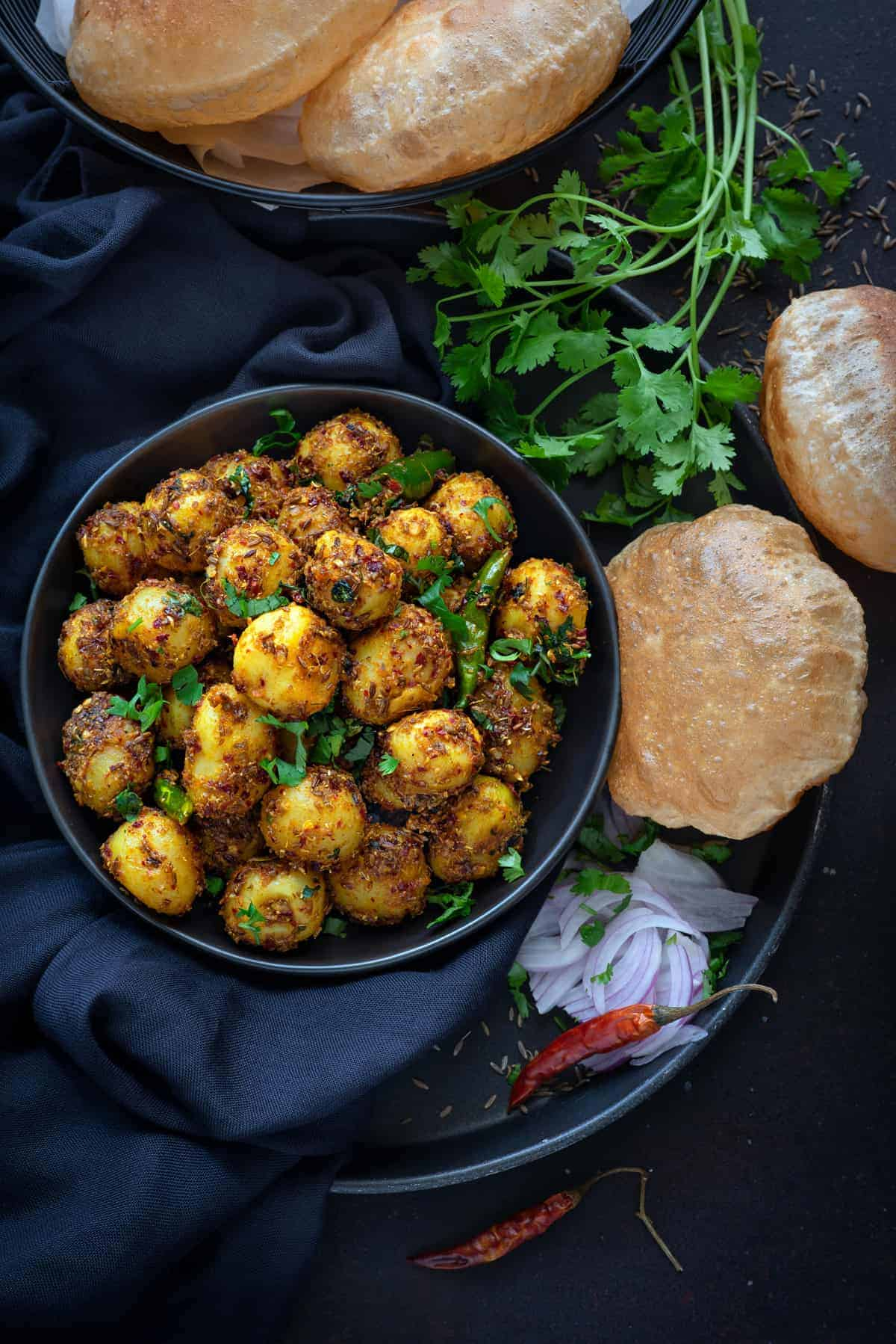 overhead shot of cumin potatoes serving on black plate with fried poori bread on the side