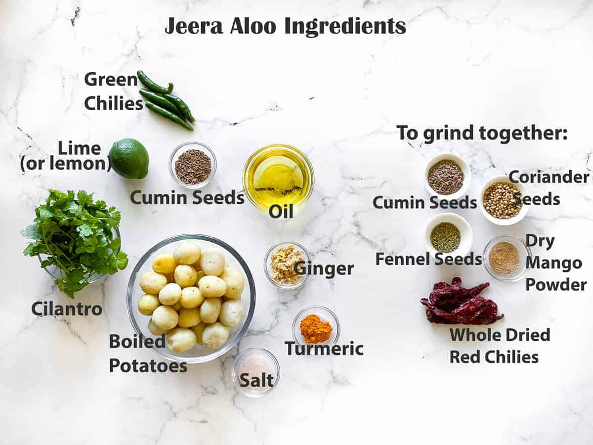mise en place for jeera aloo recipe - boiled baby potatoes, spices, seasonings, lime, chilies and cilantro