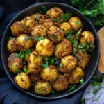 Close up shot of dry jeera aloo masala served in black plate.
