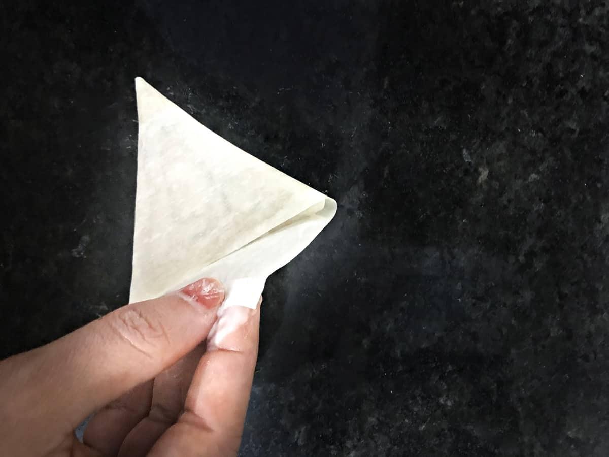 sealing the samosa patti with flour paste