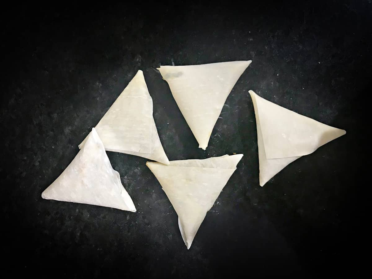 five completed wrapped keema samosa prior to frying
