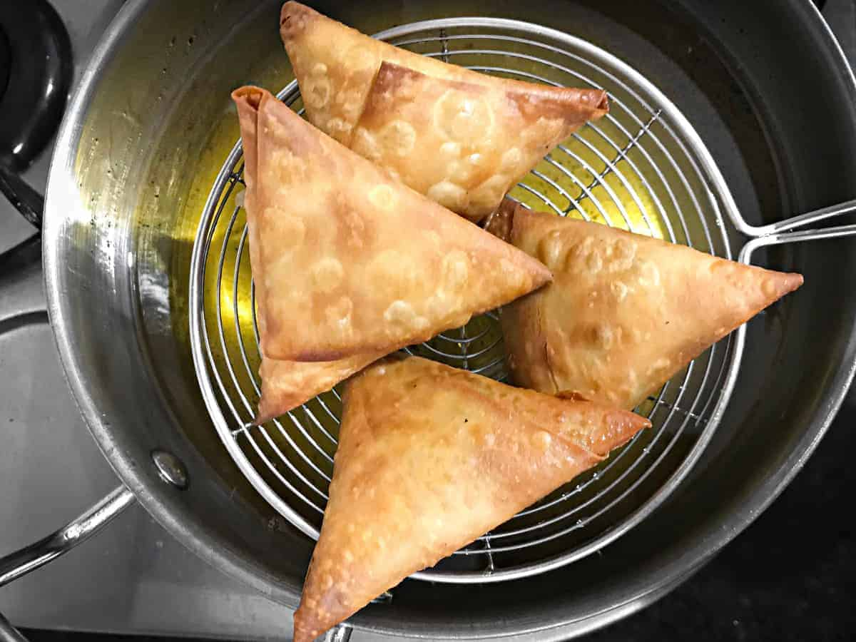 ladle lifting 4 fried keema samosa out of frying oil