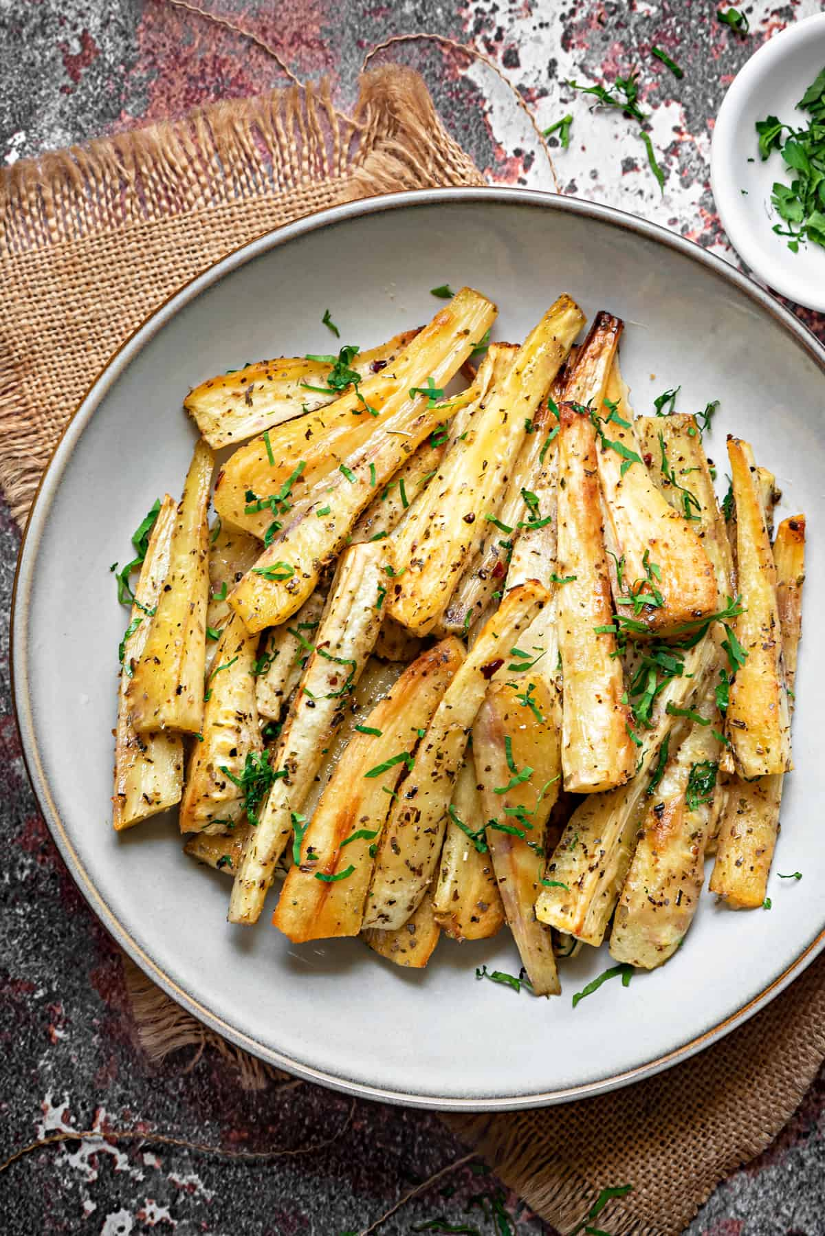 overhead shot of a pile of roasted parsnip batons on a white plate and sprinkled with fresh parsley