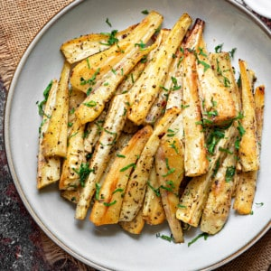 A pile of roasted parsnip batons on a white plate sprinkled with fresh parsley