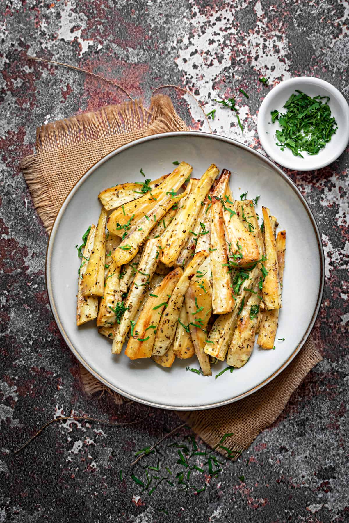 golden brown roasted parsnip batons on a white plate with fresh parsley garnish