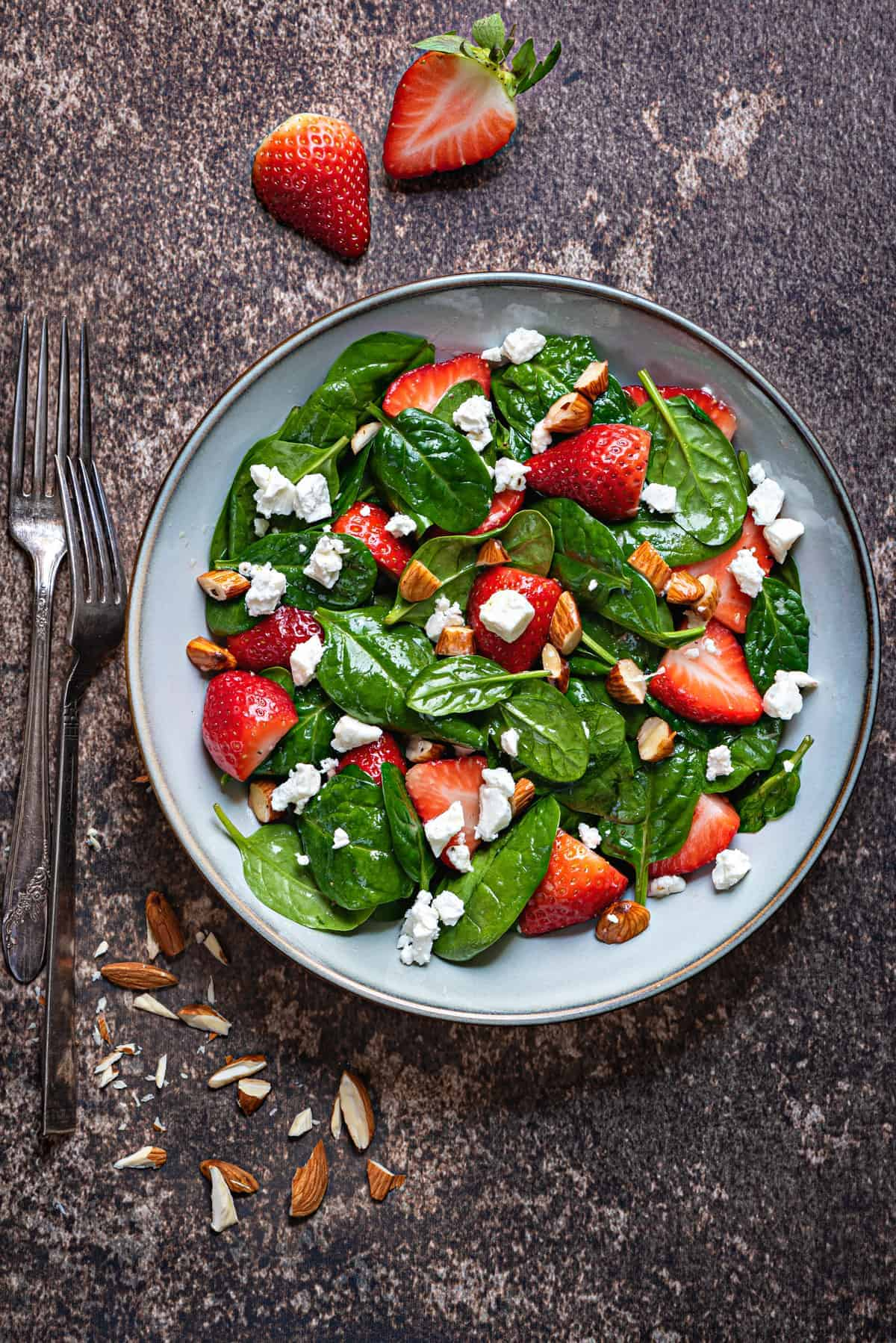 overhead shot of glazed earthenware bowl with strawberry spinach salad with almonds and feta cheese