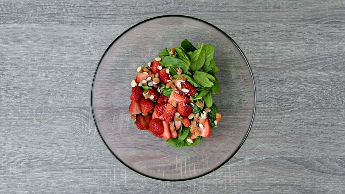 sliced strawberries, chopped almonds and fresh spinach leaves added to bowl with dressing