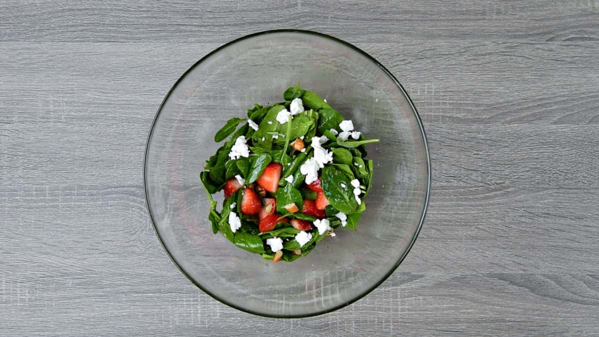 tossed strawberry spinach salad in mixing bowl topped with feta cheese crumbles