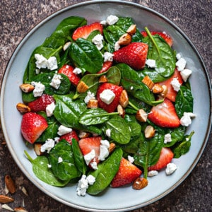 close up shot of strawberry spinach salad with feta cheese crumbles and chopped almonds
