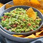 close up shot of homemade guacamole dip and yellow tortilla chips