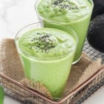 two glasses of healthy green smoothies topped with chia seeds with avocados in the background