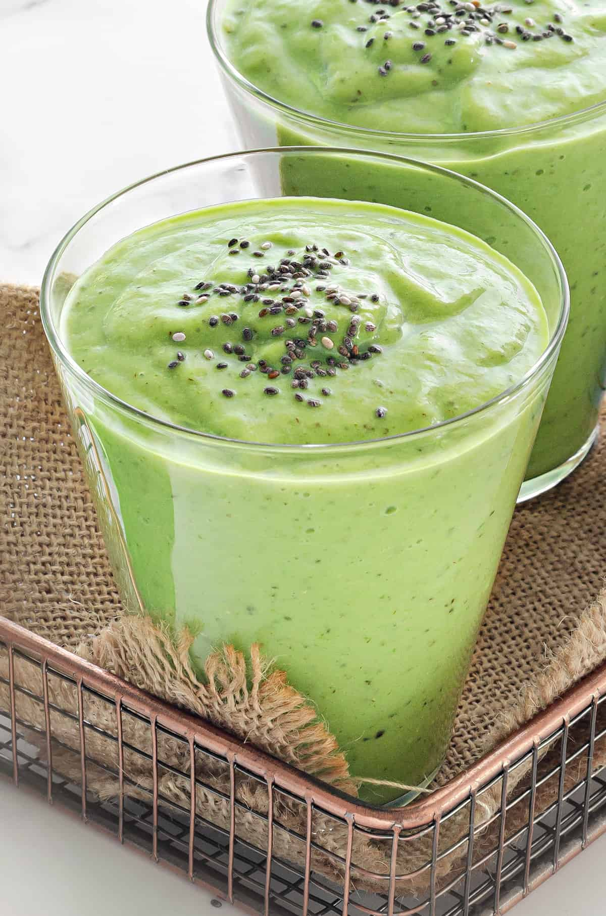 two clear glasses filled with creamy spinach avocado breakfast smoothie and topped with chia seeds