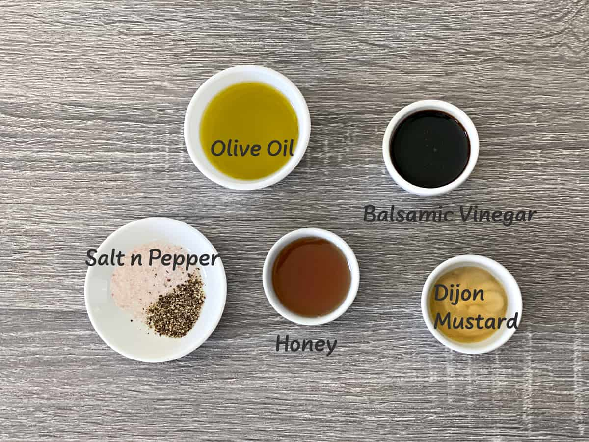 ingredients for homemade balsamic vinaigrette laid out on a grey wood table