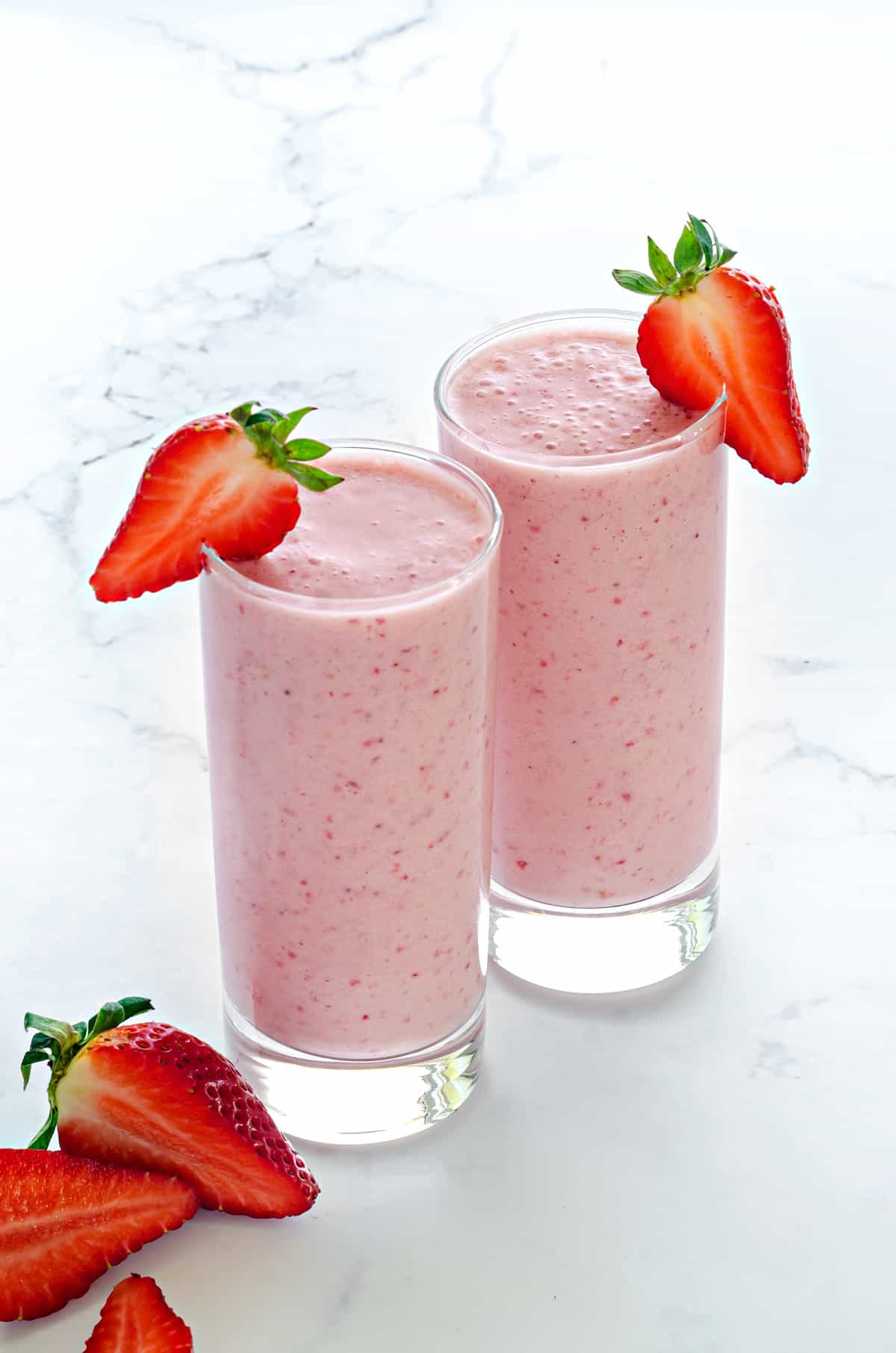 easy strawberry smoothie poured into two tall clear glasses with a fresh strawberry in the foreground