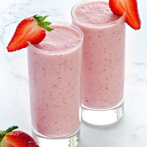 two tall clear collins glasses filled with strawberry smoothie and garnished with fresh strawberry slices