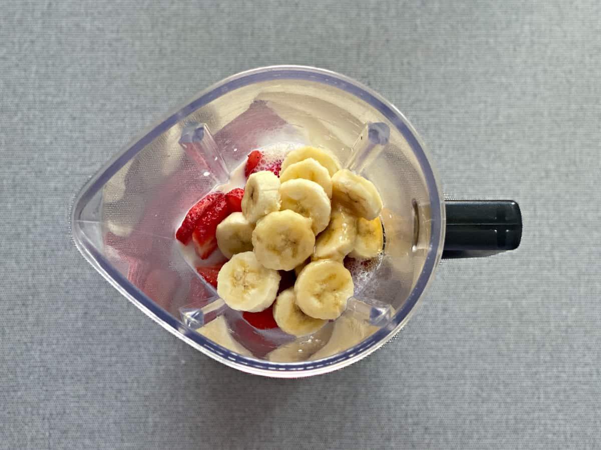 strawberry smoothie ingredients in blender pitcher