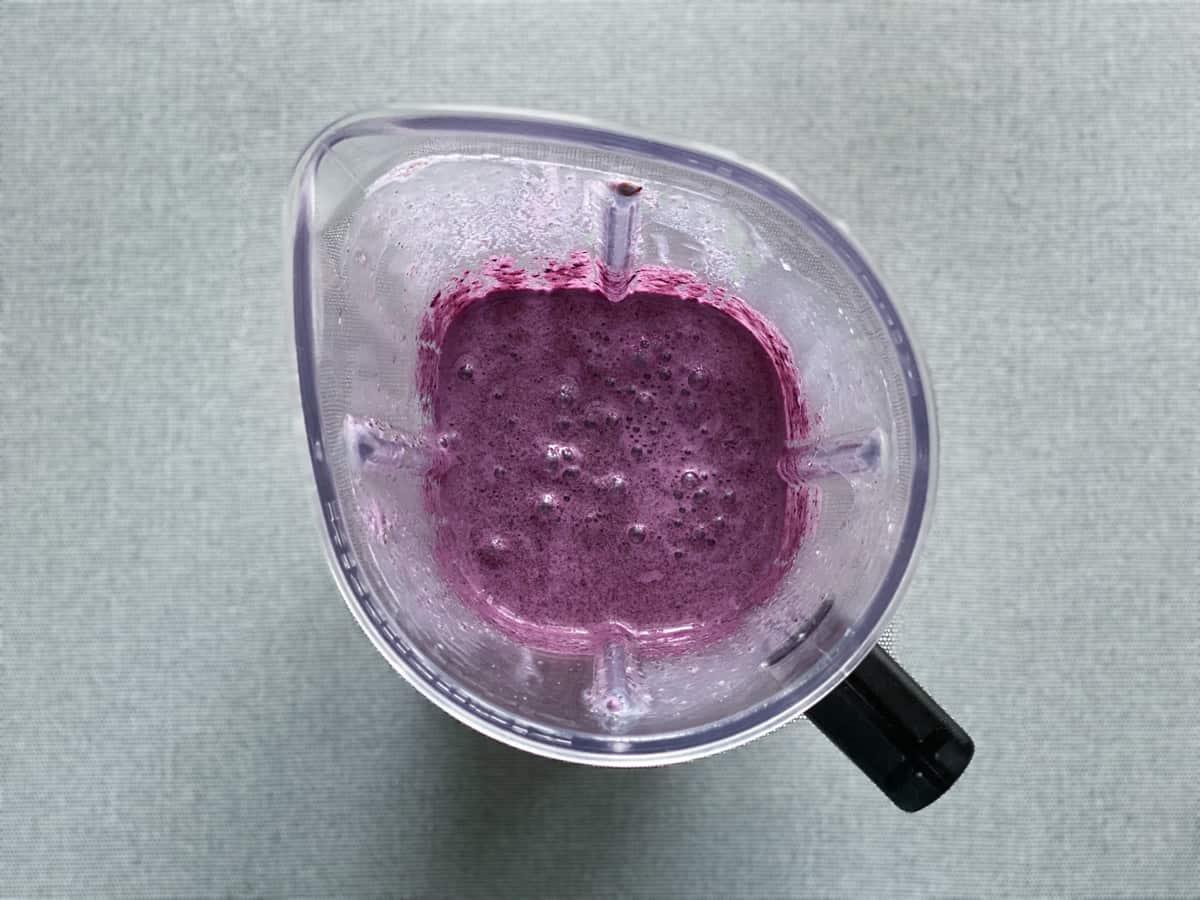 vegan blueberry almond milk smoothie after being blended in a blender