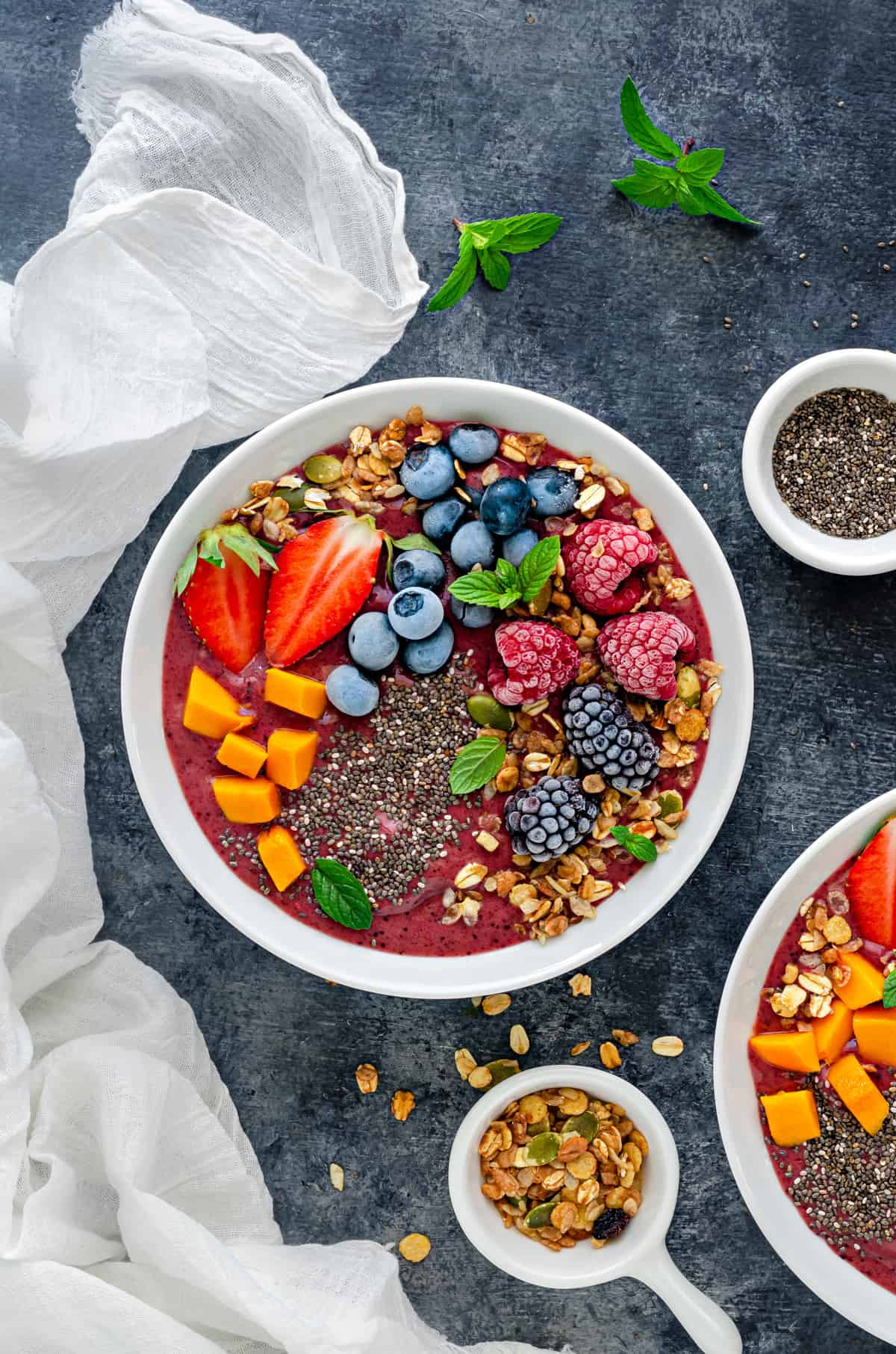 overhead shot of mixed berry smoothie bowl topped with frozen fruit, chia seeds and muesli