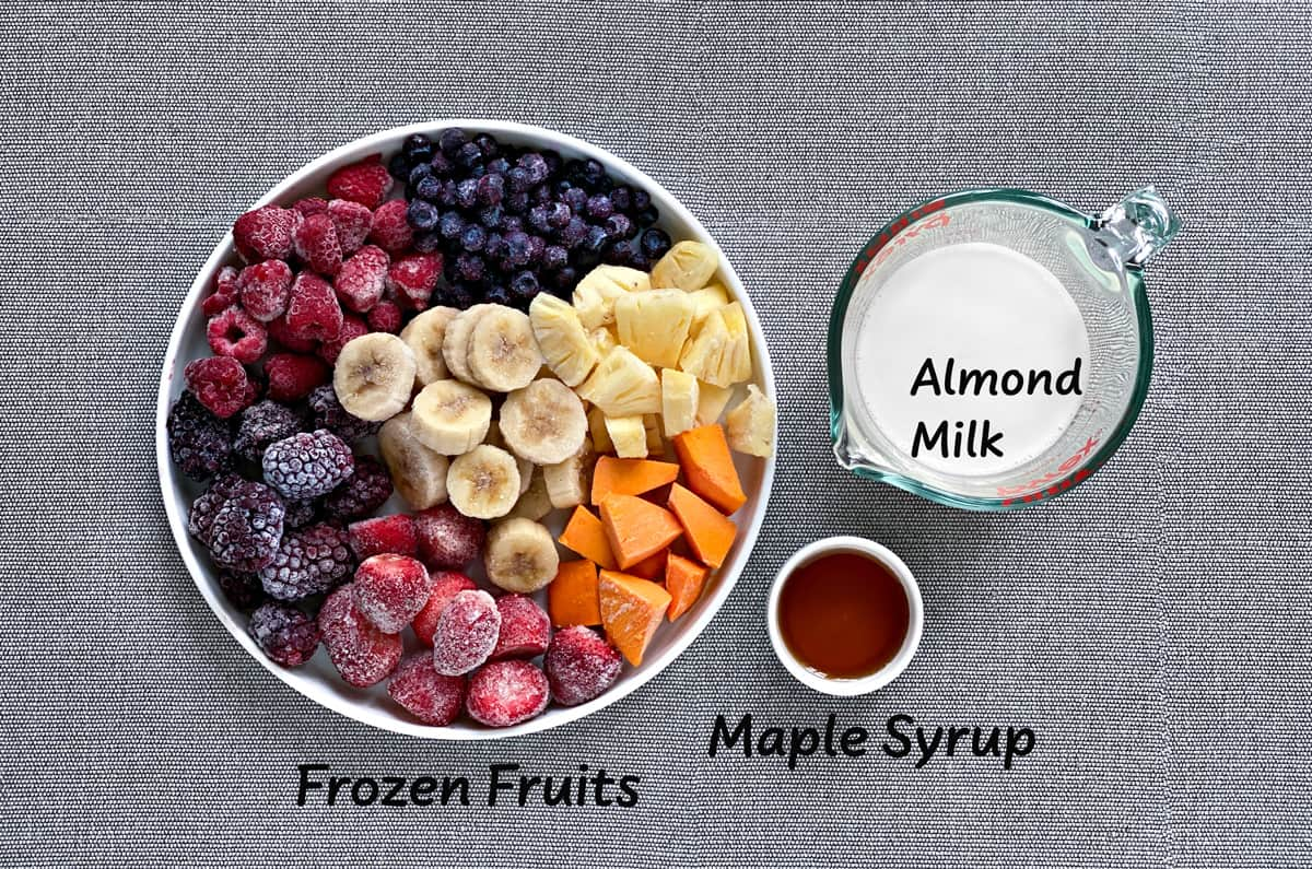ingredients for frozen fruit smoothie bowls laid out on a grey tabletop