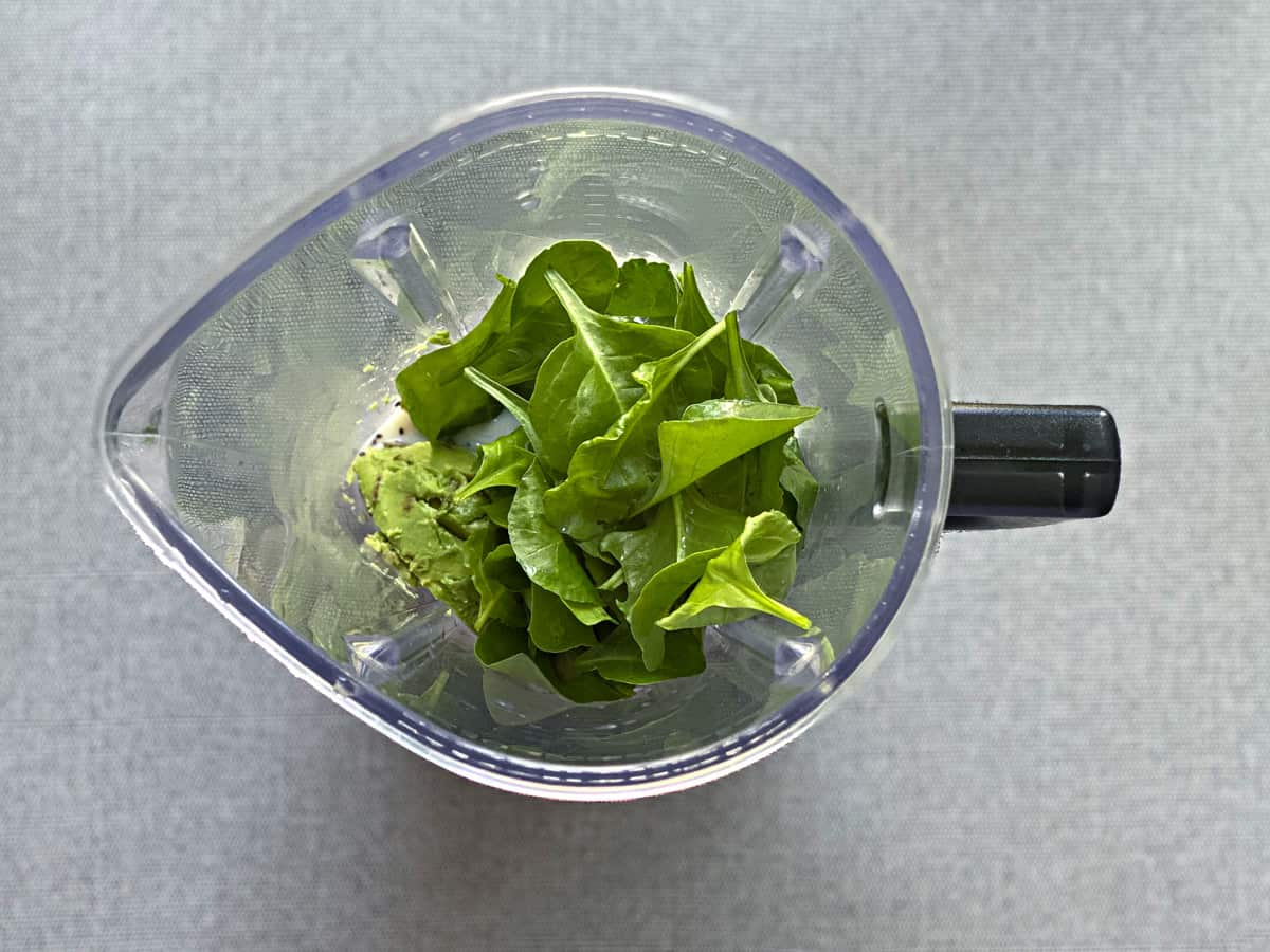 avocado breakfast smoothie ingredients in the base of a blender before blending