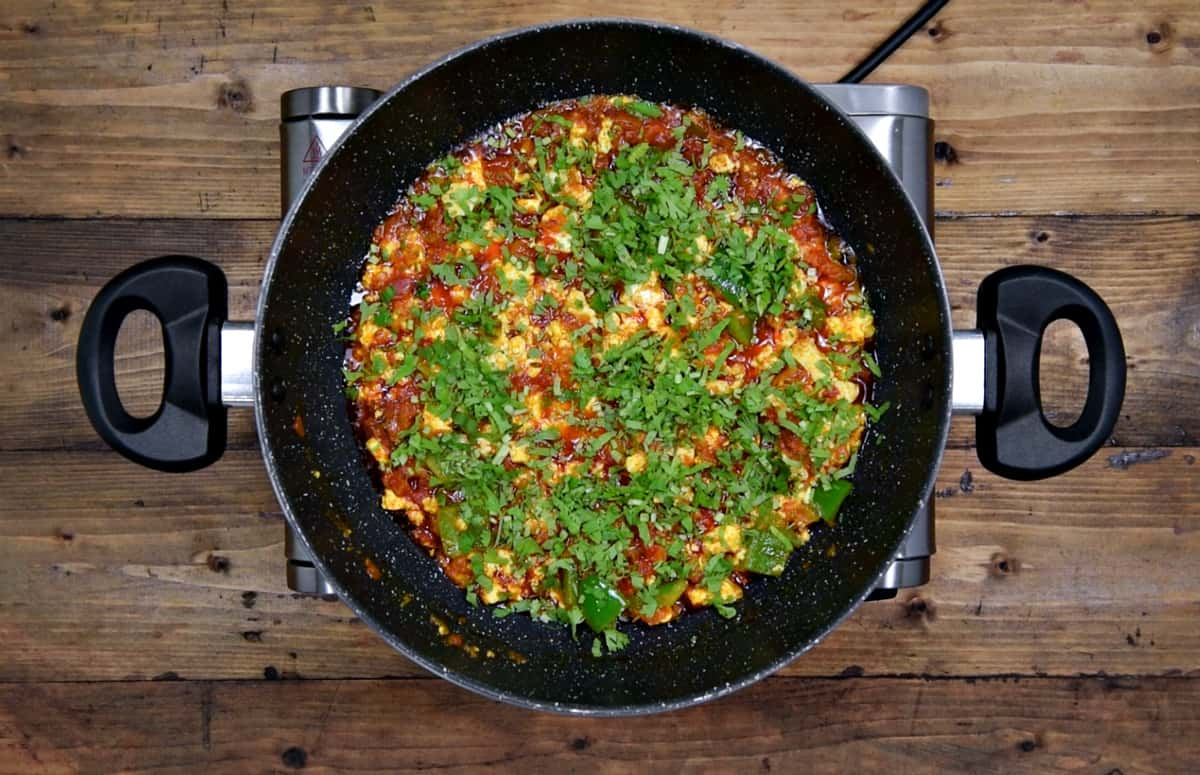 Finished paneer bhurji in pan topped with squeezed lemon and chopped cilantro