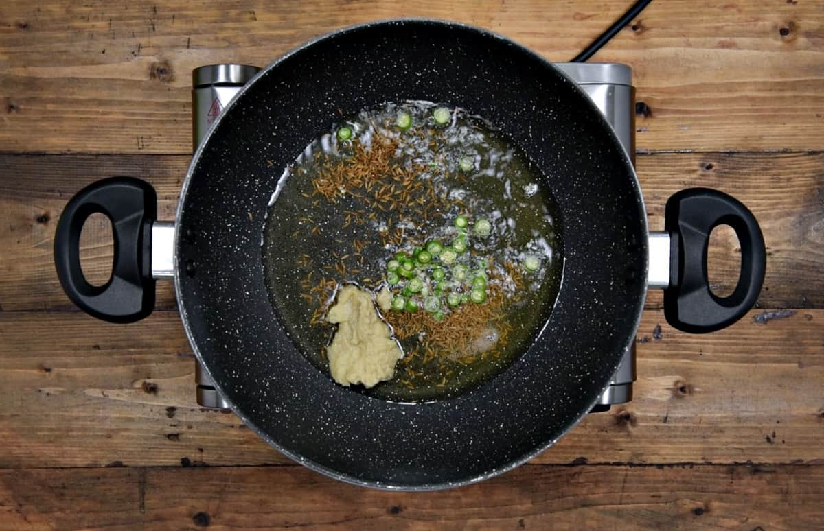 cumin, chopped chilies and ginger garlic paste added into the heated oil and butter in pan