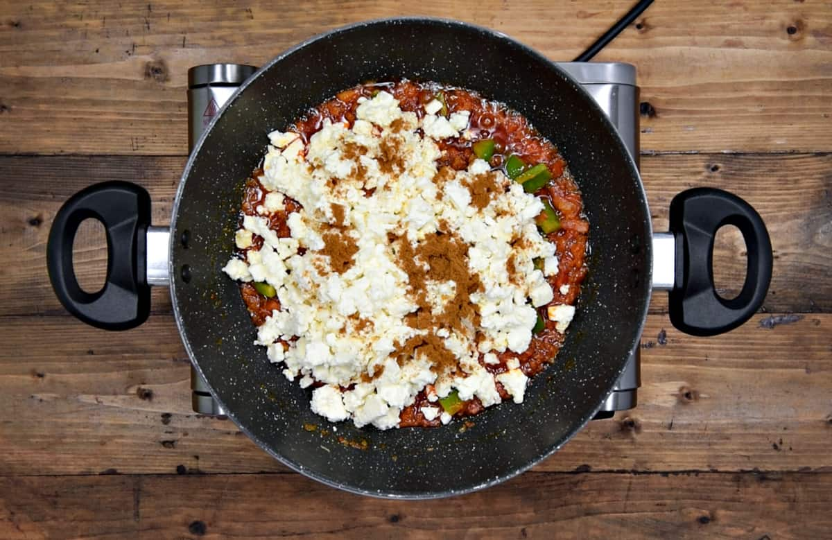 crumbled paneer and garam masala powder added to onion tomato masala in pan