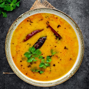 Close up shot of yellow dal served in ceramic bowl