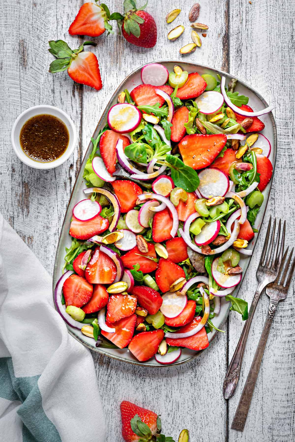 overhead shot of summer strawberry salad on a rectangular serving tray on a white wooden table