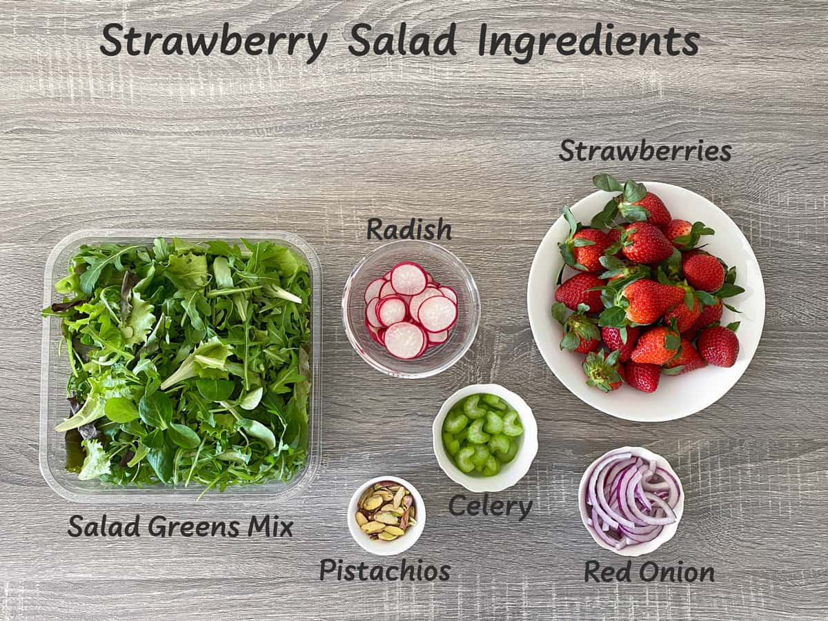 salad greens, radish, red onion, celery, shelled pistachios and fresh strawberries laid out for making a salad