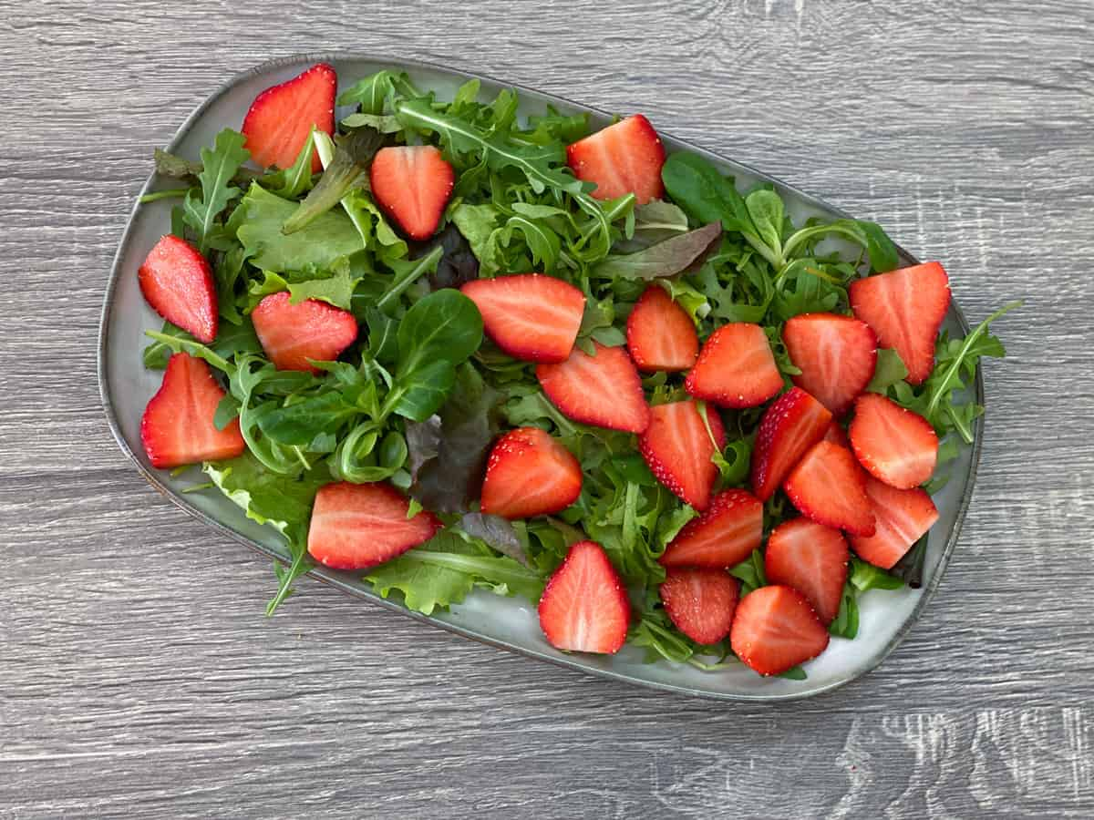 sliced strawberries added to the top of salad greens