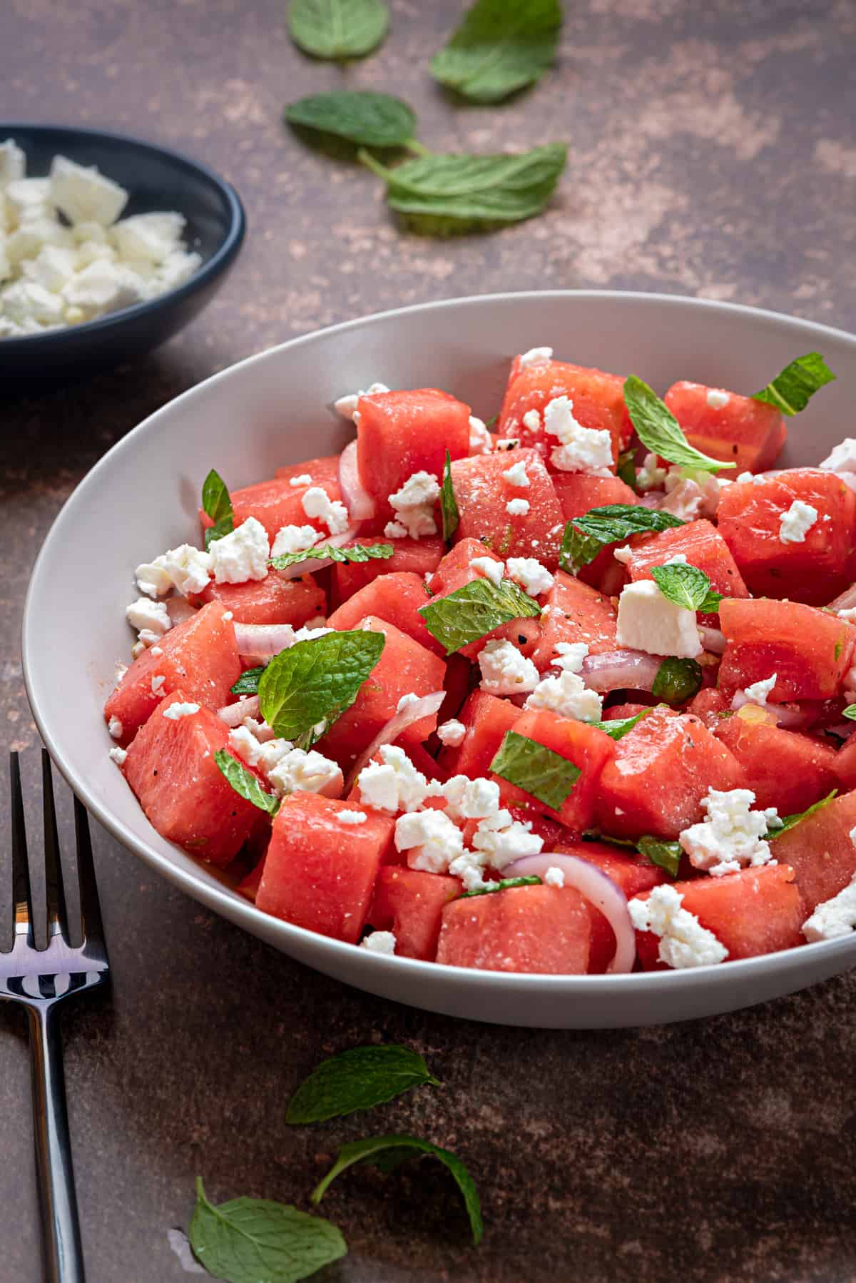 watermelon feta and mint salad in a white bowl on a brown tabletop with a silver fork