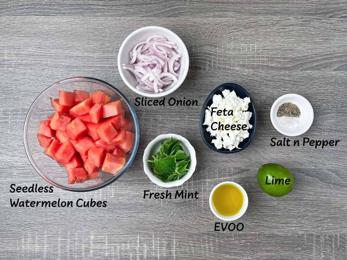ingredients for watermelon feta mint salad recipe laid out on a grey wood table