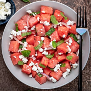 Watermelon feta salad with mint and red onions in a white bowl with a black fork