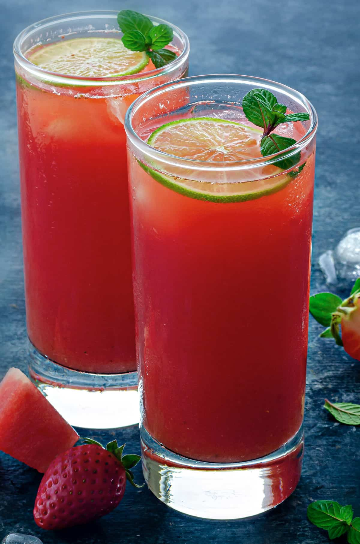 two tall collins glasses filled with watermelon strawberry lemonade
