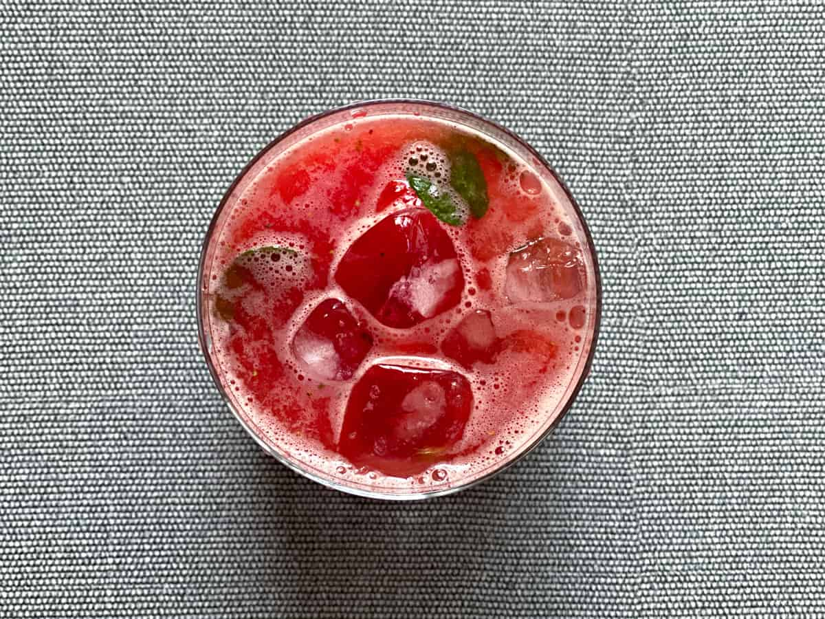 overhead shot of ginger infused watermelon strawberry lemonade in a glass with ice