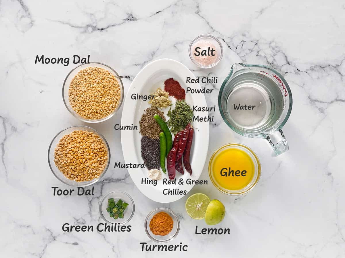 Ingredients for yellow dal recipe placed in small bowls on white table