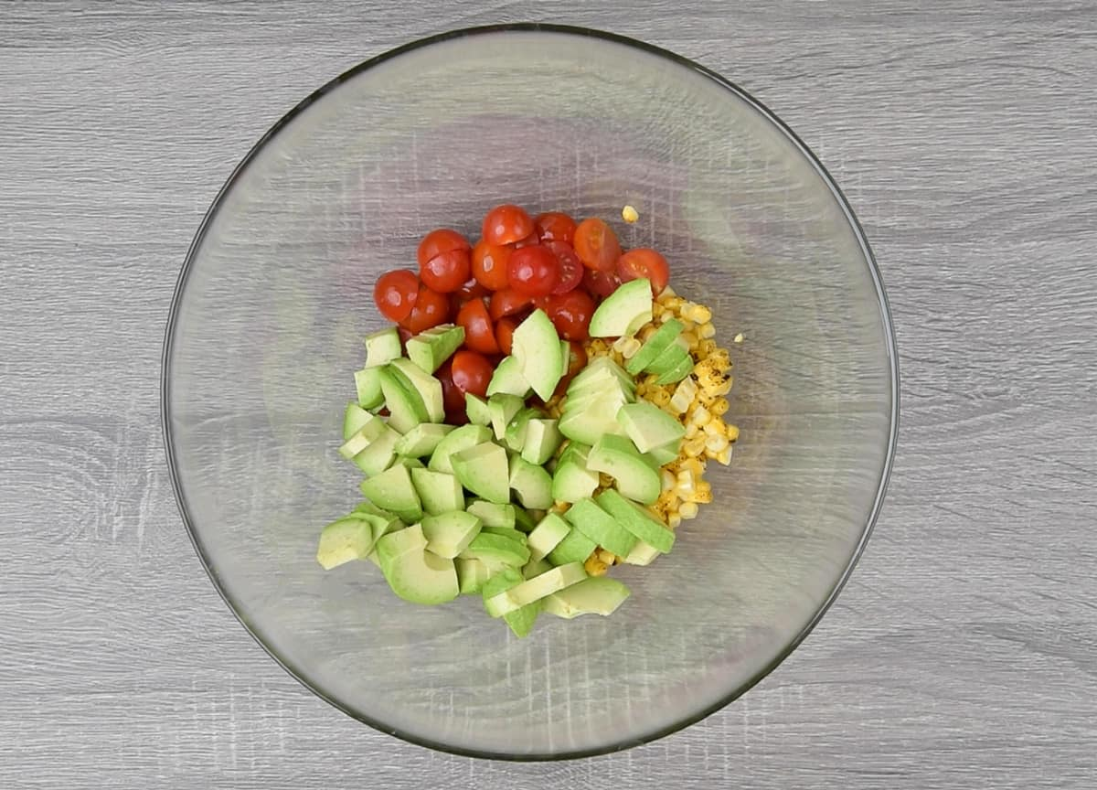 grilled corn kernels, halved cherry tomato and diced avocados in large glass bowl