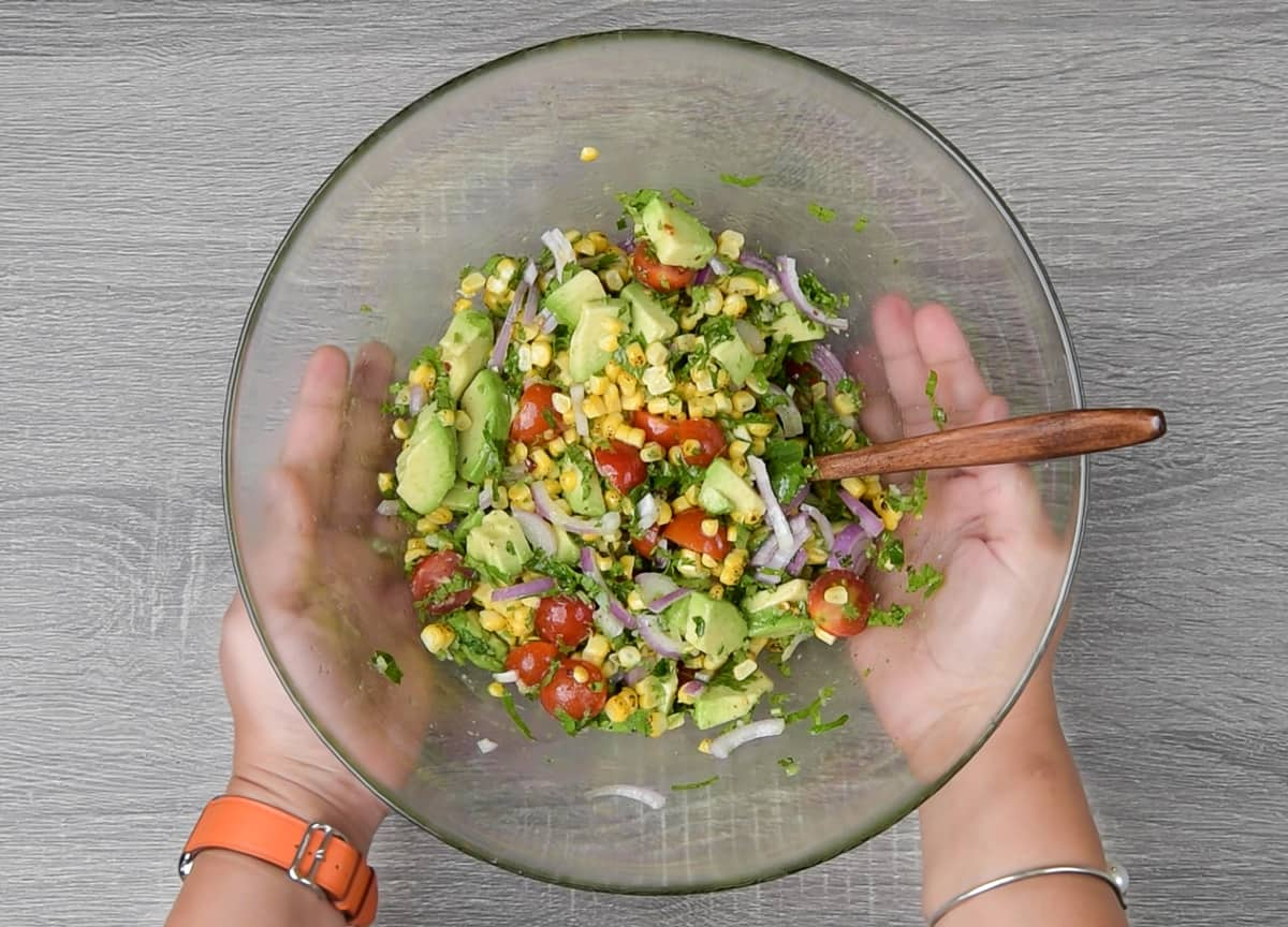 two hands holding a bowl of tomato avocado corn salad