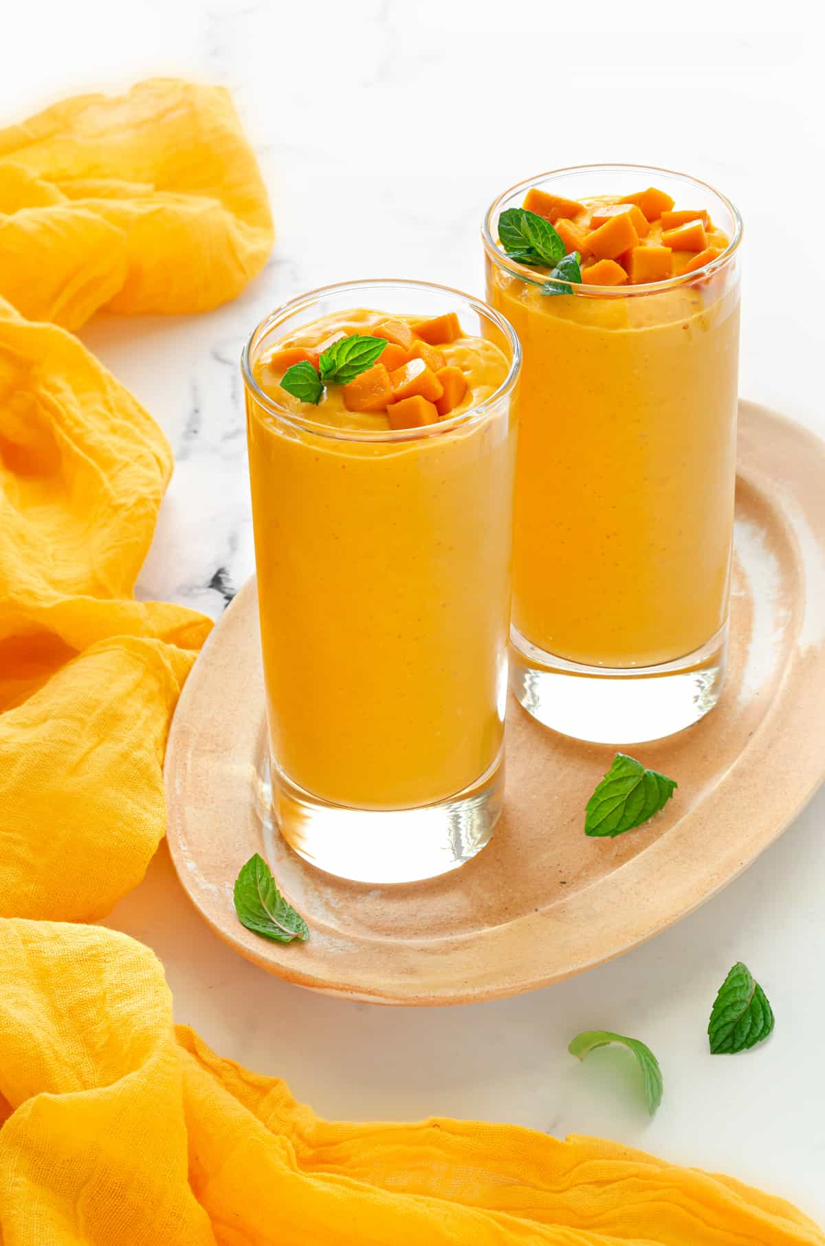 two tall collins glasses filled with mango yogurt smoothie and topped with fresh mango