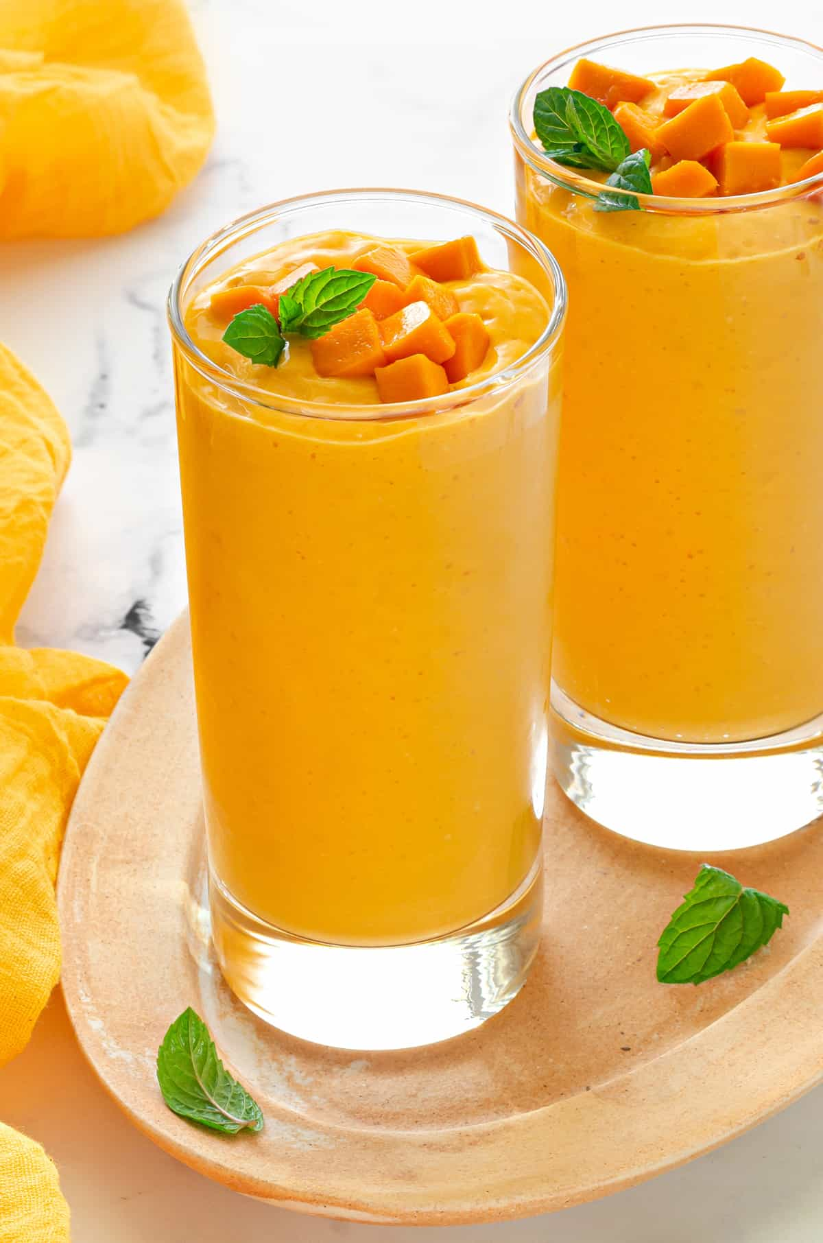 tall collins glass filled with mango oat smoothie and topped with fresh mango and mint.