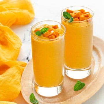 two tall collins glasses filled with yogurt mango smoothie and topped with fresh mango