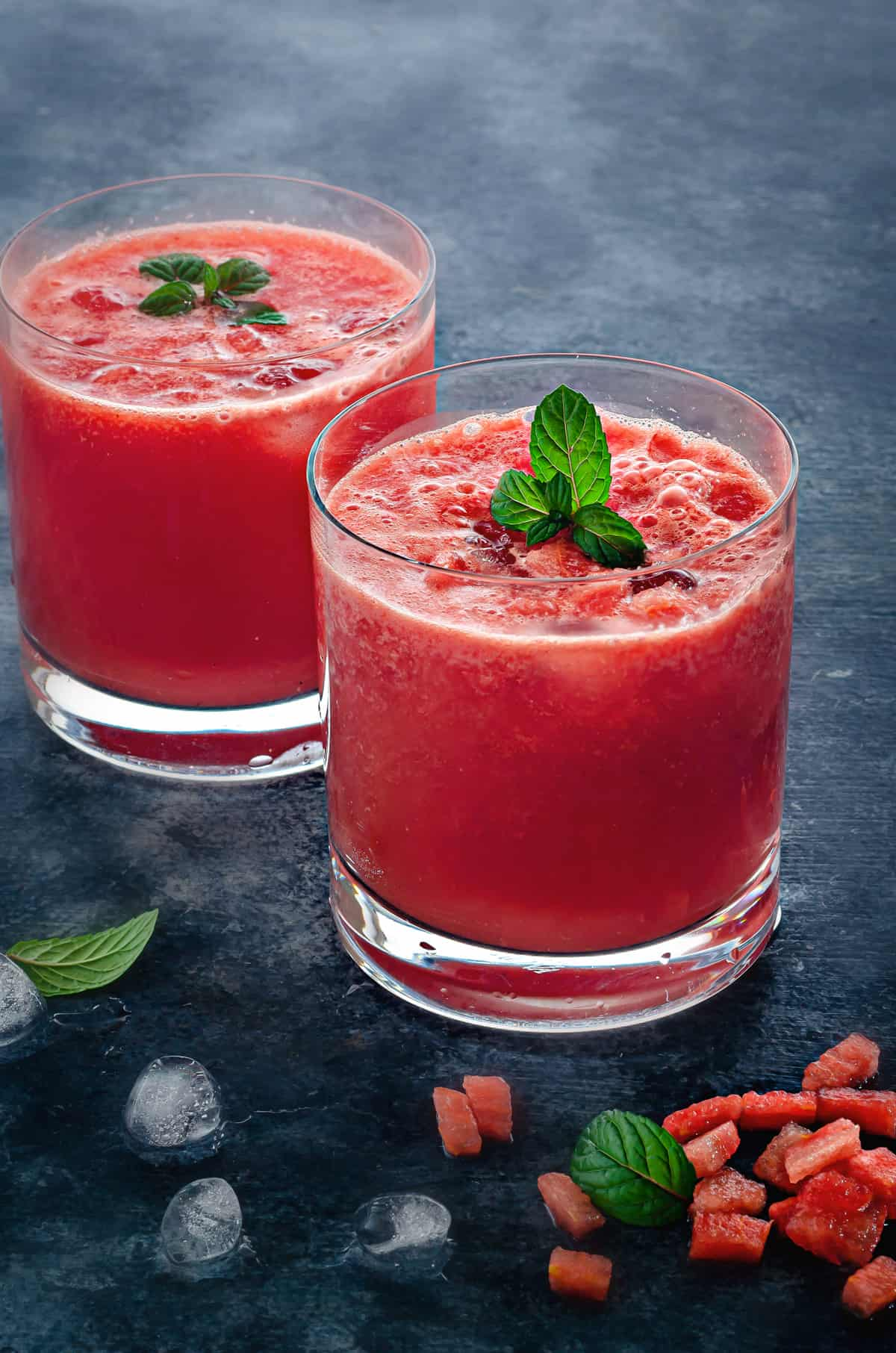 two rocks glasses of fresh watermelon juice on ice garnished with fresh mint leaves