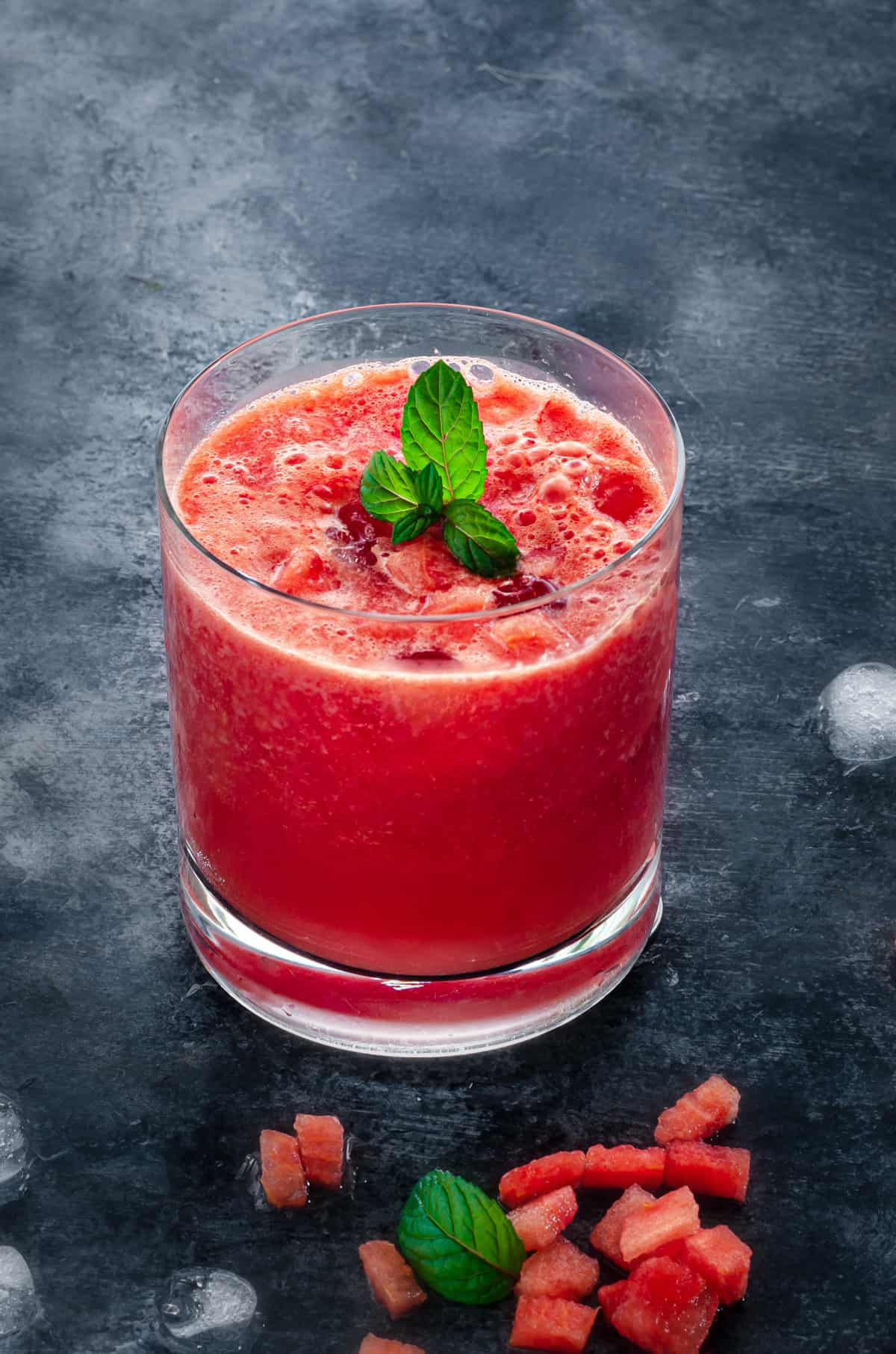short rocks glass of watermelon juice on ice with a sprig of mint