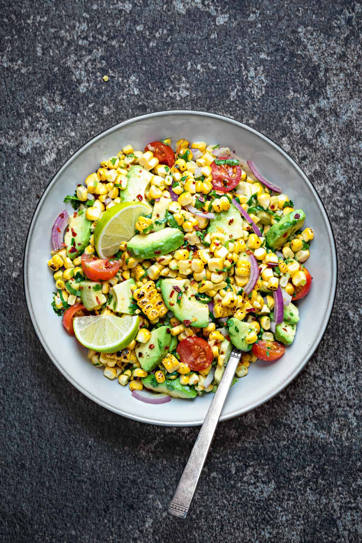Summer corn avocado salad served in grey earthen bowl with a spoon into it