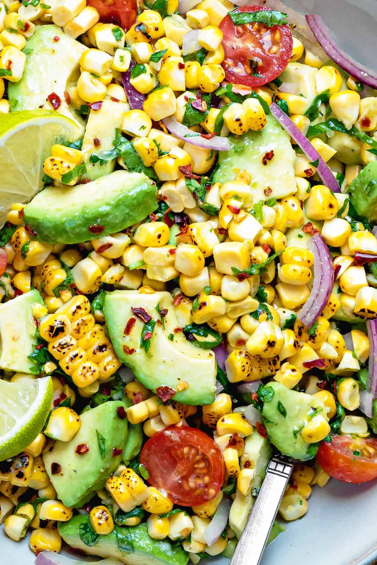 a close up shot of tomato avocado corn salad in bowl