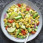 Close up shot of corn avocado salad served in ceramic bowl
