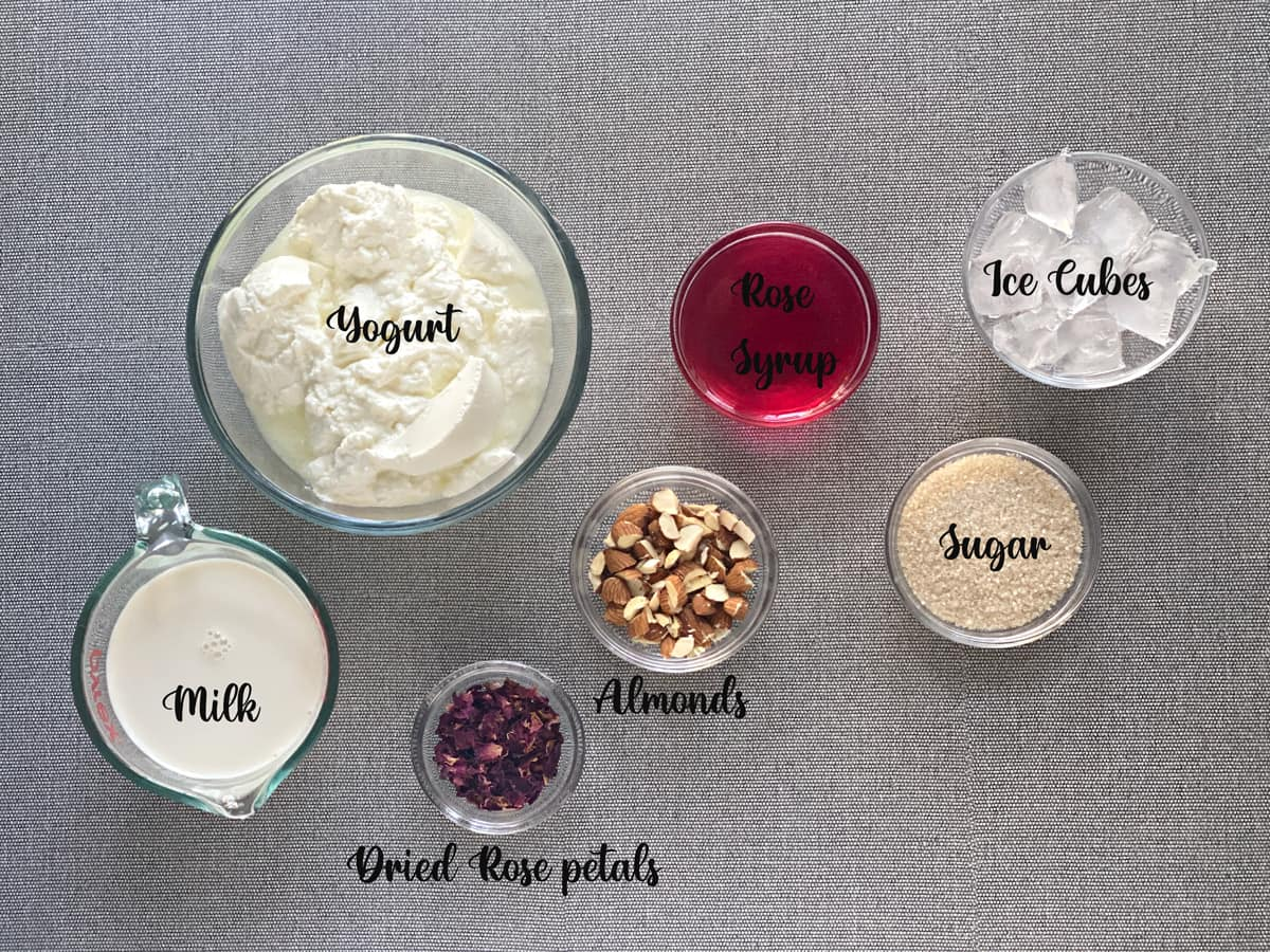 ingredients for almond rose lassi recipe placed in glass bowls and laid on grey table