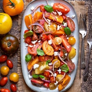 close up shot of heirloom tomato salad with feta cheese on a grey oval platter