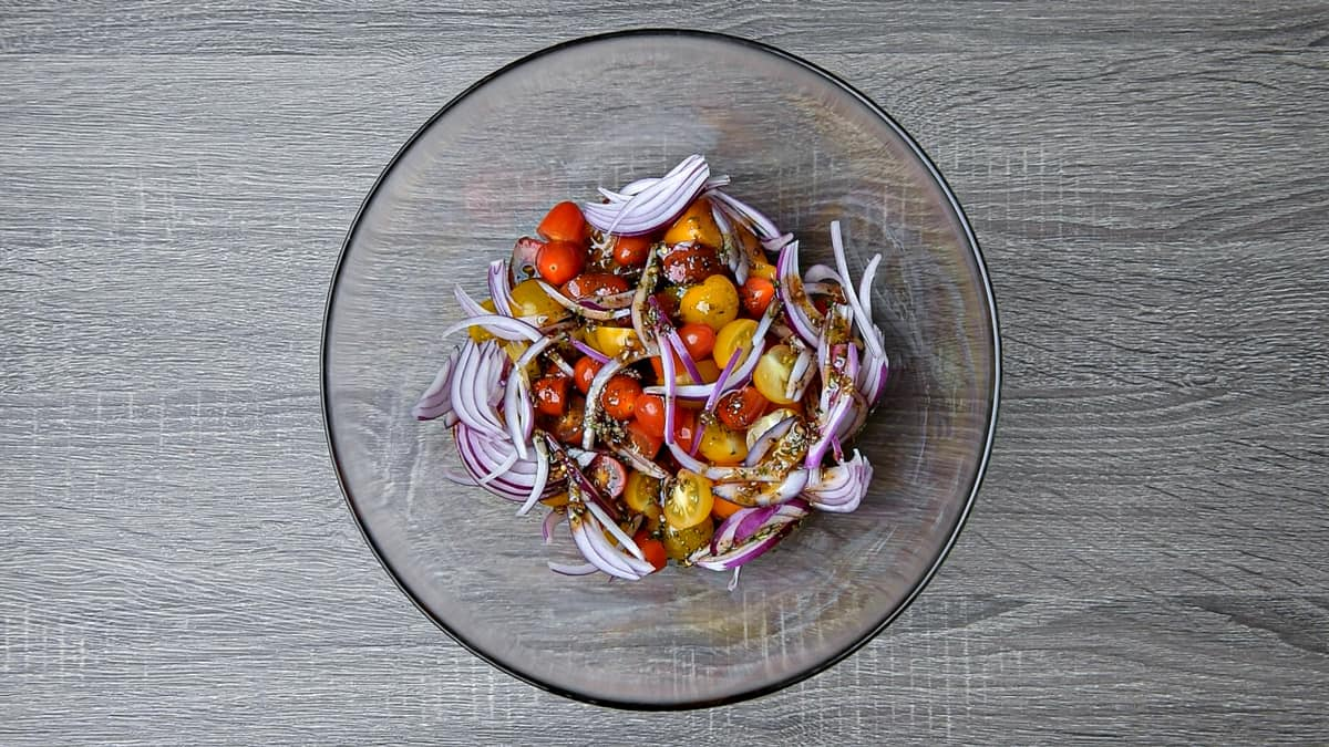 onions and dressing added to bowl of tomatoes